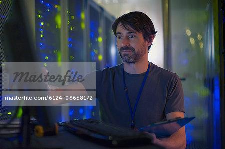 Server room technician working at computer