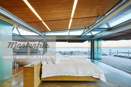 Modern luxury bedroom open to patio with ocean view