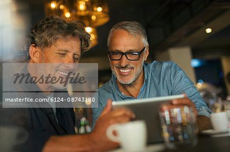 Men using digital tablet at restaurant table