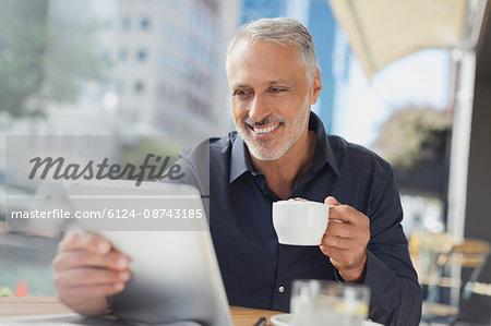 Smiling businessman using digital tablet drinking coffee at urban sidewalk cafe