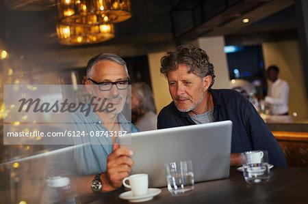 Men using laptop at restaurant