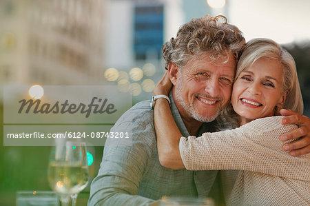 Portrait smiling senior couple hugging at urban sidewalk cafe