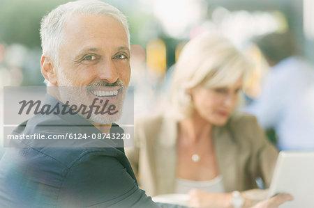 Portrait smiling businessman at sidewalk cafe