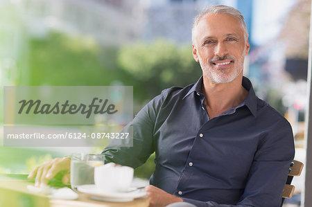 Portrait smiling man drinking coffee at urban sidewalk cafe