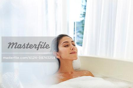 Serene woman enjoying bubble bath with eyes closed