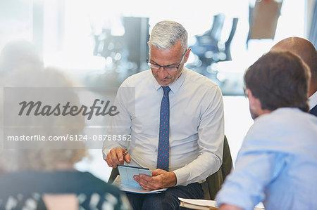 Businessman using digital tablet in meeting