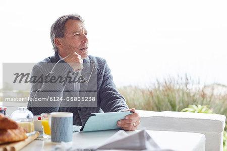 Pensive senior man using digital tablet at breakfast on patio