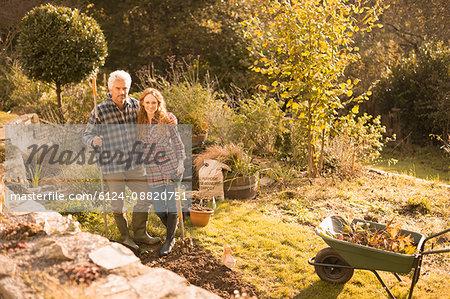 Portrait smiling couple gardening in sunny autumn garden