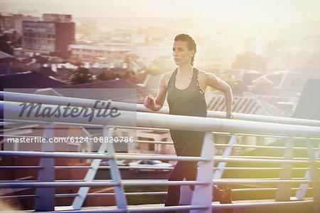Determined female runner running up urban footbridge at sunrise
