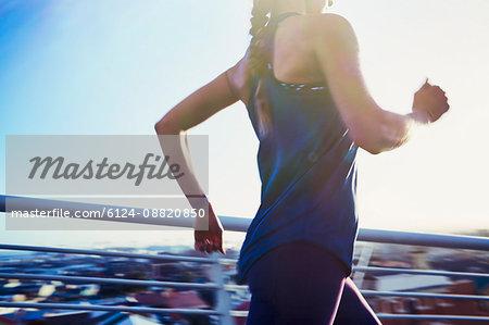 Female runner running on sunny urban footbridge