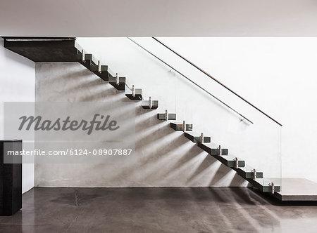 Modern, minimalist floating staircase in home showcase interior foyer