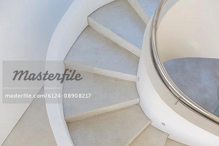 White, concrete spiral staircase in modern home showcase interior