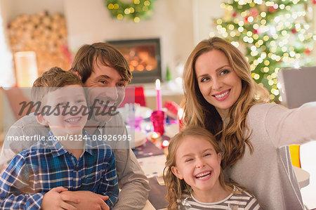 Family taking selfie at Christmas dinner table