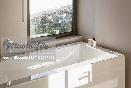 Sunny reflection over modern white bathtub below window