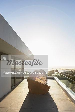Covered patio chair on sunny modern luxury balcony under blue sky