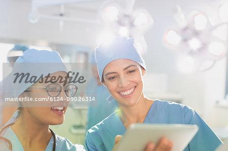 Female surgeons using digital tablet, talking in operating room