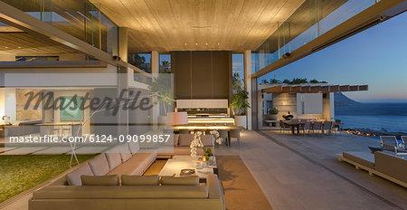 Illuminated modern, luxury home showcase interior living room open to patio at dusk