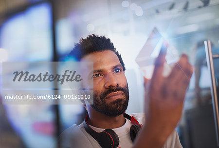 Focused, innovative male entrepreneur examining glass triangle prototype