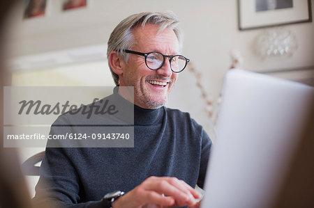 Smiling mature male freelancer working at laptop