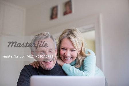 Smiling, happy mature couple using laptop