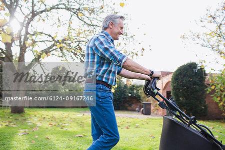 Senior man moving lawn with lawnmower in autumn backyard