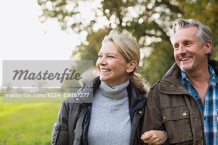 Happy, carefree mature couple in autumn park