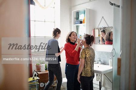 Young women friends getting ready, applying music in bathroom