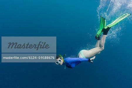 Portrait young woman snorkeling underwater