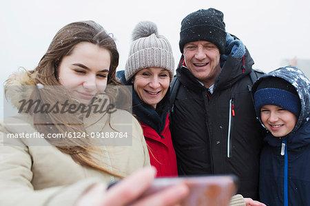 Snow falling on smiling family taking selfie