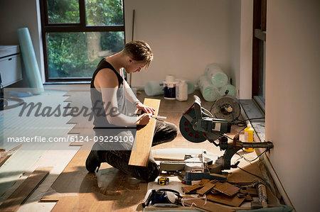 Construction worker preparing hardwood flooring in house
