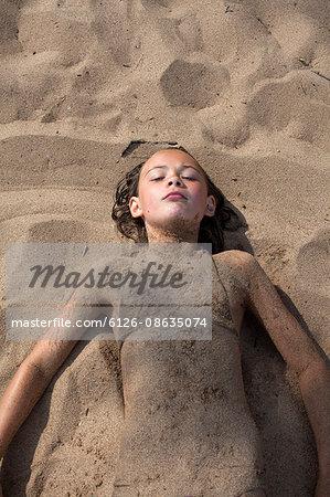 Sweden, Dalarna, Girl (10-11) lying in sand on beach