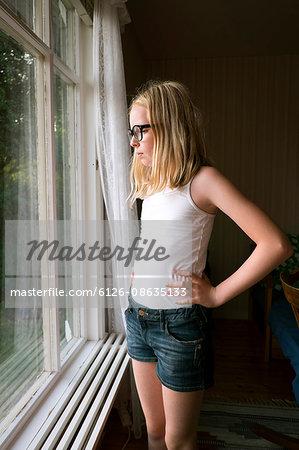 Sweden, Skane, Vejbystrand, Girl (10-11) looking though window