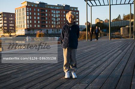 Sweden, Sodermanland, Hammarby Sjostad, Portrait of boy (6-7) standing on pier