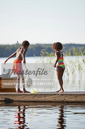 Sweden, Vastra Gotaland, Skagern, Girl (6-7) and boy (10-11) fishing in lake