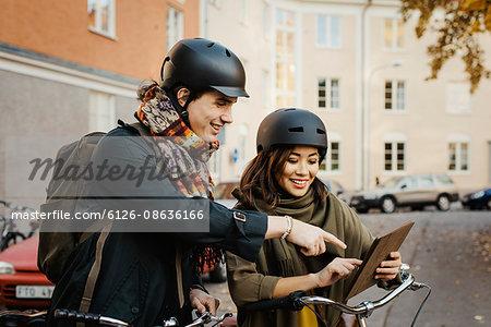 Sweden, Uppland, Stockholm, Vasastan, Rodabergsbrinken, Two young people looking at digital tablet smiling