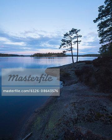 Sweden, Vastergotland, Tiveden National Park, Stora Trehorningen, Lake at sunset under cloudy sky