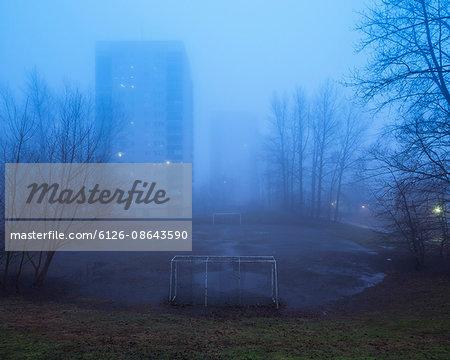 Sweden, Skane, Malmo, Hogaholm, Almvik, Residential buildings with soccer field in foreground in fog