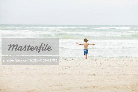 Denmark, Vendsyssel, Jutland, Lokken, Boy (8-9) standing on beach