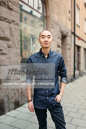 Sweden, Sodermanland, Stockholm, Sodermalm, Smiling young man on sidewalk