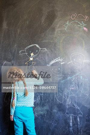 Finland, Girl (4-5) drawing on chalkboard