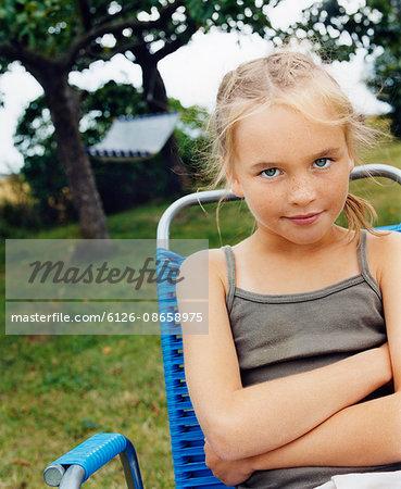 Sweden, Blonde girl (10-11) sitting in folding chair in garden