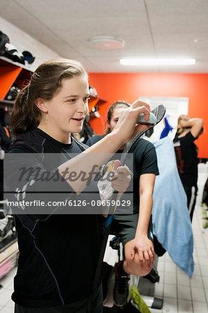 Sweden, Young woman waxing hockey stick in locker room