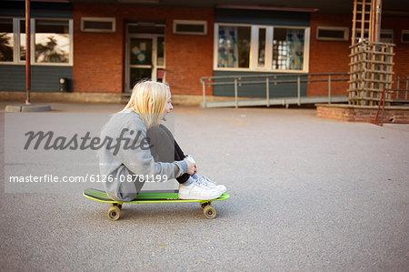 Sweden, Vastergotland, Lerum, Girl (12-13) sitting on skateboard
