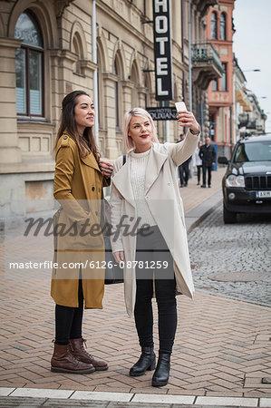 Sweden, Skane, Kirstianstad, Two young women taking selfie photo on street