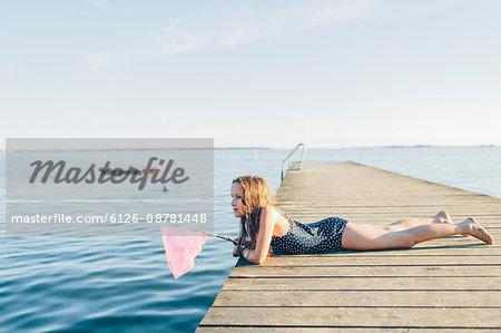 Sweden, Blekinge, Karlskrona, Salto, Girl (10-11) lying on pier and fishing