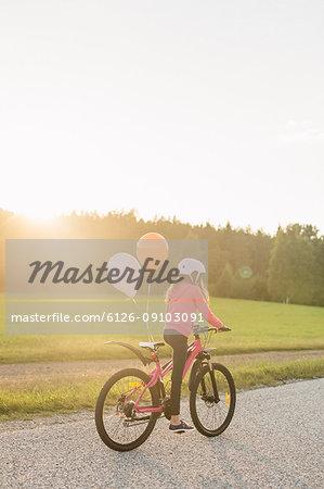 Girl riding bicycle at sunset