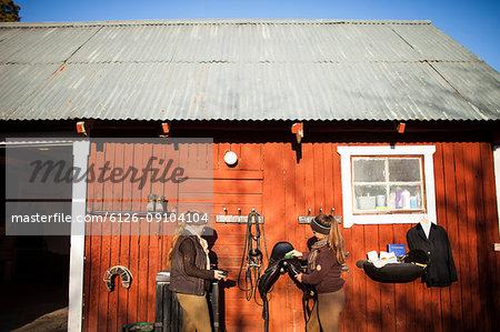Women standing in front of barn