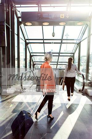 Rear view of businesswomen walking towards escalator at railroad station