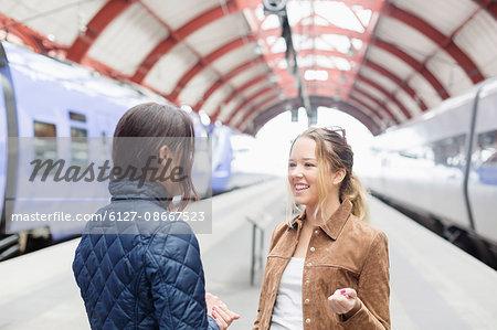 Female friends communicating on railway station