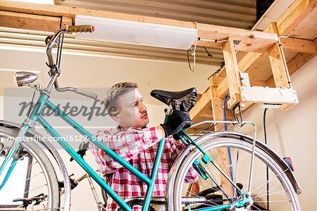 Mid adult repairman fixing bicycle seat in workshop